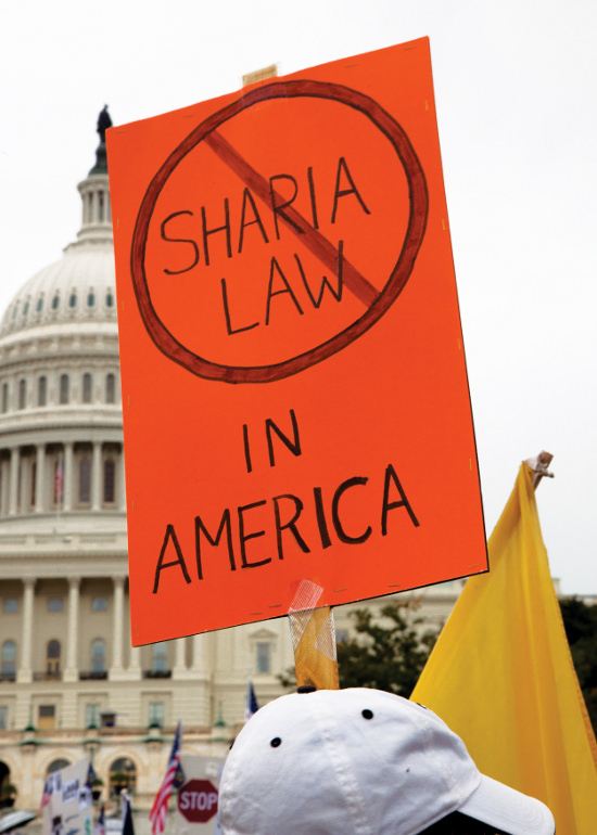 Protester holding a sign that says no Shari'a Law in America in from of the US Capital Building