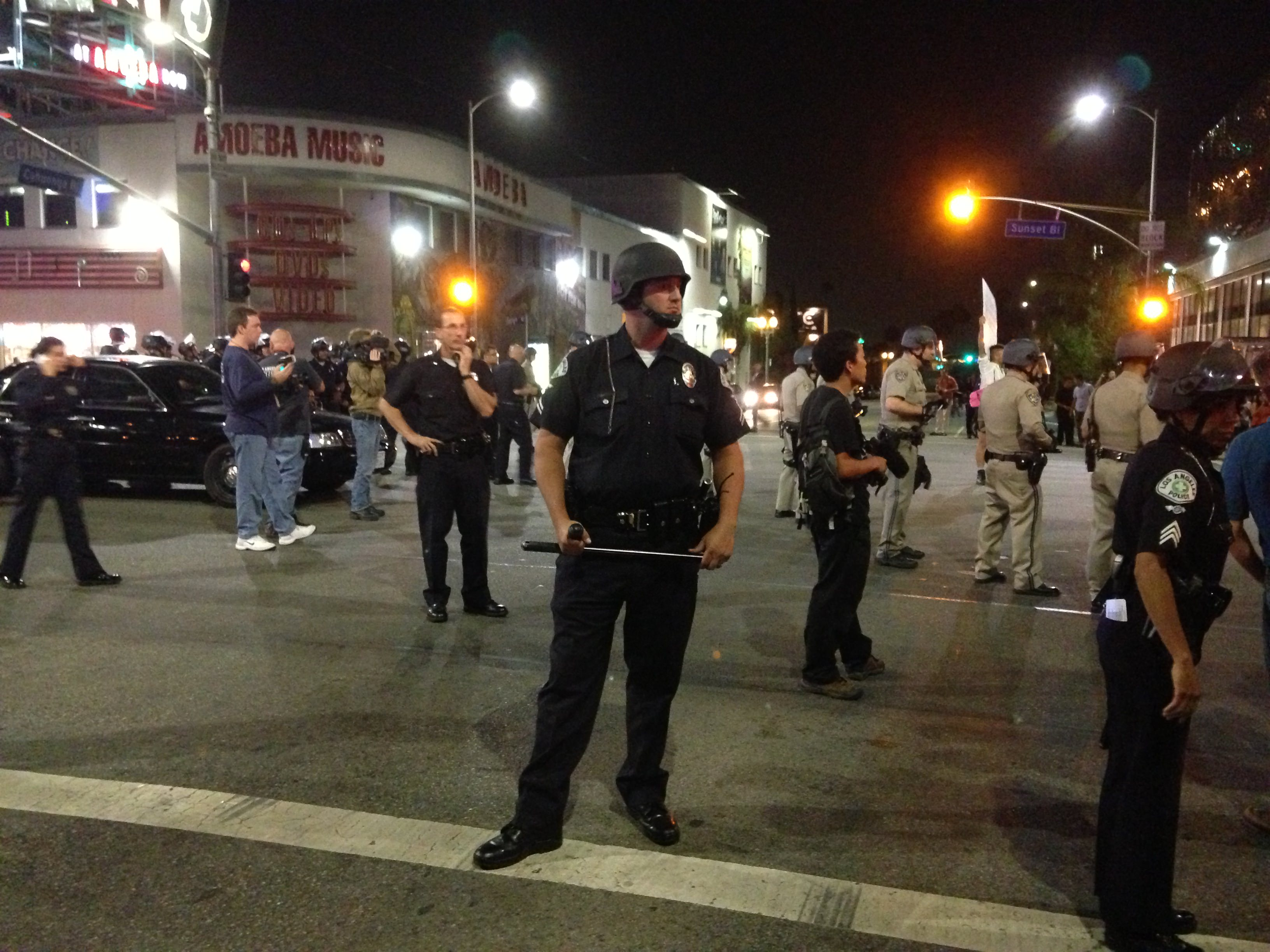 LAPD officer holds night stick as a part of a police line in Hollywood, Calif.